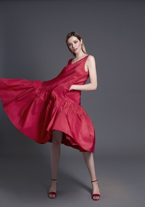 Vestido de tafetán rojo con vuelo de WOMAN FIESTA y sandalia roja de ZENDRA (todo de EL CORTE INGLÉS)